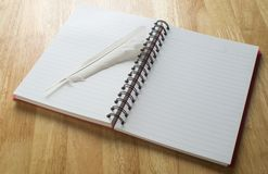 Feather on paper. White feather placed on notebook paper Stock Photo