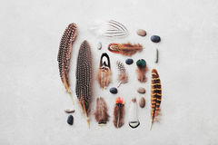 Feather pattern with pebble on gray stone background top view in flat lay style for boho theme. Feather pattern with pebble on gray stone background from above Royalty Free Stock Photo