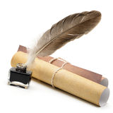 A feather pen, ink,rolls of old yellowed paper. On a white background royalty free stock photography