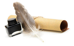 A feather pen, ink,rolls of old yellowed paper. On a white background stock photo