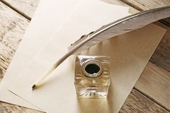 Feather pen with inkwell and blank papers. On wooden background Royalty Free Stock Image