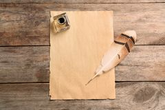 Feather pen, inkwell and blank parchment on wooden table, top view. Space for text royalty free stock photo