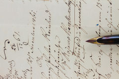 Feather pen. Old  golden feather pen on  handwritten letter background close up Stock Photo
