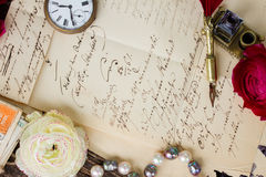 Feather pen. Old paper with ink stains and old letter with flowers, antique watch and feather pen Royalty Free Stock Images