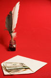 Feather quill, ink and money Stock Images