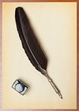 Feather quill and inkwell on an old paper Stock Image