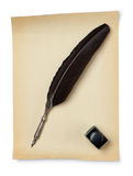 Feather quill and inkwell on an old paper Royalty Free Stock Photos