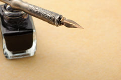 Feather quill and inkwell on an old paper Royalty Free Stock Image