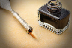 Feather quill and inkwell on an old paper Stock Photography