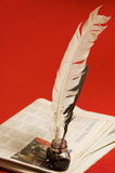 Feather quill and newspapers Stock Image