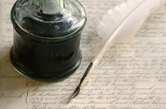 Feather quill pen and inkwell. With background of 19th century writing stock photos