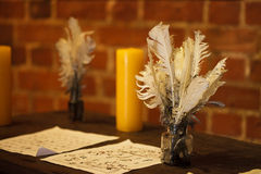 Feather quill pens candle and old paper on wooden desk. Vintage. Royalty Free Stock Images