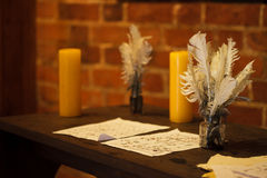 Feather quill pens candle and old paper on wooden desk. Vintage. Stock Images