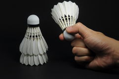Feather shuttlecock on hand. With black background royalty free stock images