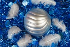 Feather and silvery Christmas ball on a blue tinsel. Feather and silvery bauble on a blue tinsel as decoration for Christmas Royalty Free Stock Photo
