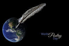 Feather standing on a blurred earth globe against a black background, sample text World Poetry Day, March 21 stock photography