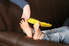 Feather tickling bare feet. Bare feet being tickled by feather royalty free stock photos
