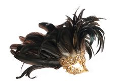 Feathered mask. A golden feathered Venetian mask isolated on a white background Stock Photo