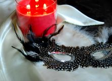 Feathered Mask by Candle. Sexy feathered masquerade mask by lit candle Royalty Free Stock Photography