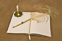 Feathered Pen Lying On Blank Open Journal. A blank lined journal with a feathered quill pen lying on it on a brown background stock images