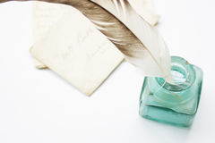 Feathered Quill. A feathered quill pen standing in a glass ink pot with old hand written letters behind, set on a white background Stock Photo