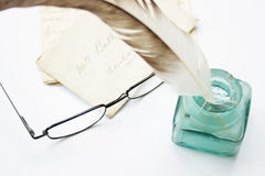 Feathered Quill, ink pot & glasses. A feathered quill pen standing in a glass ink pot with old hand written letters behind, set on a white background Royalty Free Stock Images