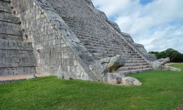 Feathered serpent at the base of the stairs of the El Castillo Pyramid at at Chichen Itza archeological site, Mexico. royalty free stock photo