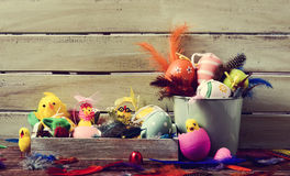 Feathers, toy chicks and decorated easter eggs. A pile of different decorated easter eggs, some toy chicks and feathers of different colors against a rustic Royalty Free Stock Image
