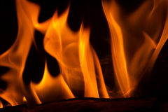 Feathery Orange Flames. A long exposure image of orange flames on burning logs in a fireplace Royalty Free Stock Image