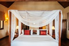 Asian tropical bedroom four poster bed white curtain and wooden closet stock photography