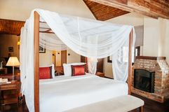 Asian tropical bedroom four poster bed white curtain and fireplace royalty free stock images