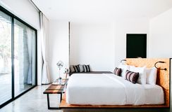 White contemporary hotel style bedroom with white linen high ceilling and vintage floor fan. FEB 23, 2015 Kanchanaburi, Thailand : White contemporary hotel style stock image