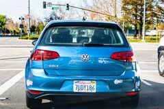 Feb 27, 2020 San Jose / CA / USA - Back view of blue Volkswagen e-Golf driving on a busy city street; VW e-Golf is the electric