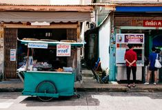 Songkhla, THAILAND - Local colourful turqouise old tricycle street food stall selling snack next to ice cream shop on royalty free stock image
