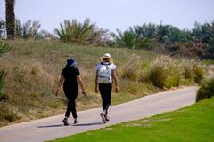 Feb 26, 2018: Two young women walking on jogging track at Saadiyat Island Golf course, Abu dhabi royalty free stock image