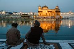 24 febbraio 2018 Amritsar, India Due Sikh indiani equipaggia si siede vicino all'acqua del tempio dorato alla notte Fotografia Stock Libera da Diritti