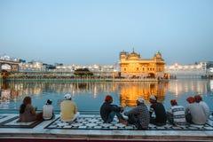 24 febbraio 2018 Amritsar, India Il gruppo di Sikh indiani equipaggia si siede vicino all'acqua del tempio dorato alla notte Fotografia Stock