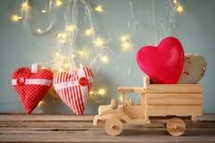 14 febbraio calendario d'annata di legno con il camion di legno del giocattolo con i cuori davanti alla lavagna Fotografia Stock