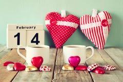 14 febbraio calendario d'annata di legno con il cioccolato variopinto di forma del cuore accanto alle tazze delle coppie sulla ta Immagini Stock