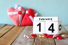 14 febbraio calendario d'annata di legno con il cioccolato variopinto di forma del cuore sulla tavola di legno Fuoco selettivo Fotografia Stock Libera da Diritti