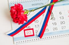 23 febbraio carta festiva Garofano rosso, bandiera tricolore russa e calendario con data il 23 febbraio incorniciato Fotografia Stock