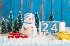 24 febbraio Cubi il calendario per il 24 febbraio su superficie di legno con il pupazzo di neve, la slitta, la neve e l'abete Immagini Stock