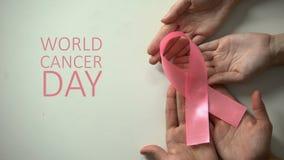 4 febbraio iscrizione di giorno del cancro del mondo, mani della gente che tengono nastro rosa video d archivio