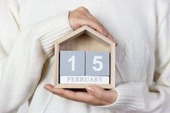 15 febbraio nel calendario la ragazza sta tenendo un calendario di legno Giorno internazionale del Cancro di infanzia, bandiera n Immagine Stock