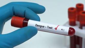 Febbre rompiossa-prova, medico che tiene campione di sangue in primo piano del tubo, controllo generale di salute archivi video