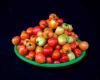 22, febrero El tomate 2017 de Dalat- da fruto en la cesta plástica verde, fondo negro Imagen de archivo libre de regalías