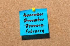 Febrero - nombre del mes de invierno con la tacha noviembre, diciembre y enero en la etiqueta engomada azul fijada en el tablón d Fotos de archivo libres de regalías