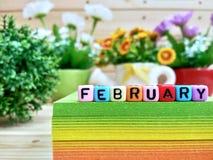 februar Bunte Würfelbuchstaben auf klebrigem Anmerkungsblock lizenzfreies stockfoto