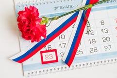 23. Februar festliche Karte Rote Gartennelke, russische dreifarbige Flagge und Kalender mit gestaltetem Datum am 23. Februar Stockfoto