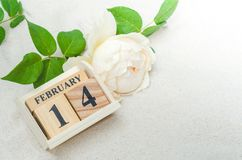 14. Februar hölzerner Kalender mit rosafarbener Blume auf Sandhintergrund Lizenzfreie Stockbilder